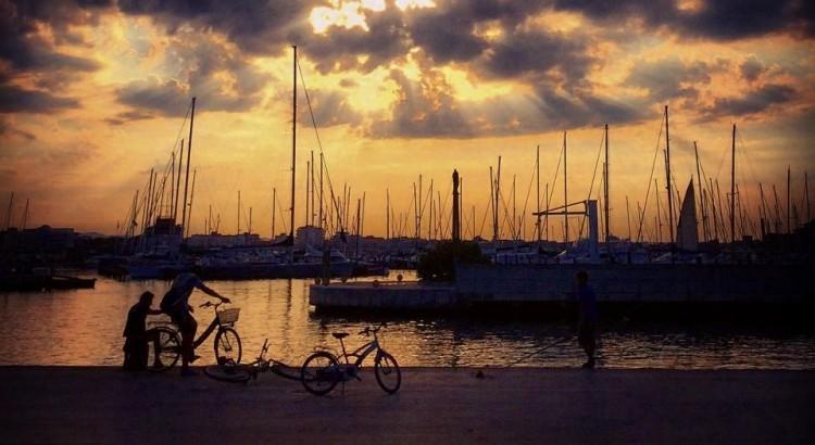 tramonto porto barche a vela e biciclette